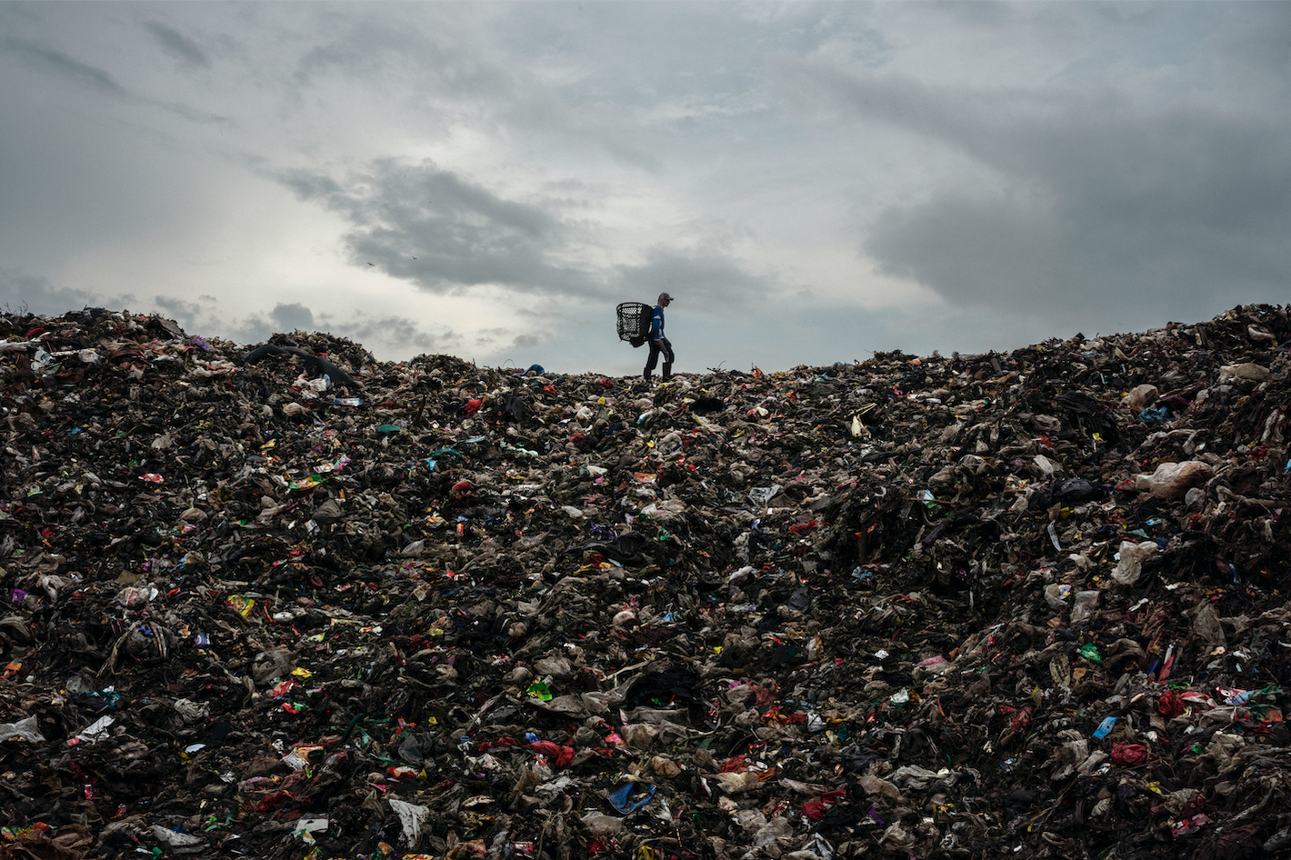 man-walks-on-top-of-rubbish-pile