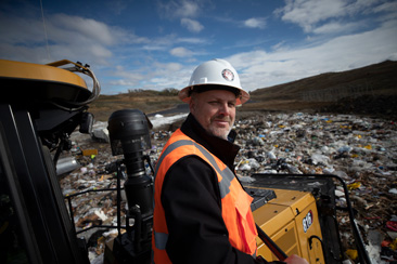 Worker stands in front of the Cat 816 Landfill Compactor